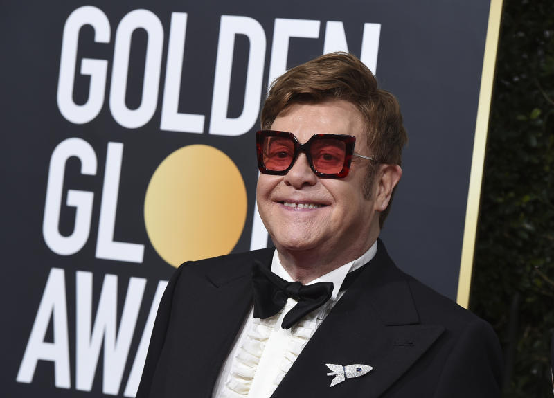 FILE - In a Sunday, Jan. 5, 2020 file photo, Elton John arrives at the 77th annual Golden Globe Awards at the Beverly Hilton Hotel, in Beverly Hills, Calif. Celebrities from Elton John to Chris Hemsworth have each pledged to donate a million to help aid the efforts for the engulfing wildfires in Australia. (Photo by Jordan Strauss/Invision/AP, File)