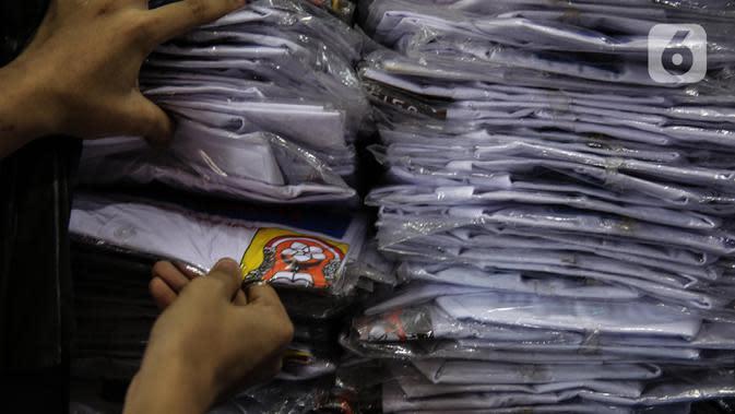 Penjual melihat seragam sekolah dagangannya di kawasan Pasar Jatinegara, Jakarta, Selasa (30/6/2020). Sejumlah pedagang di tempat itu mengeluhkan omset penjualan seragam sekolah yang menurun hingga 90 persen akibat sepi pembeli dan anjuran belajar di rumah saat COVID-19. (Liputan6.com/Faizal Fanani)