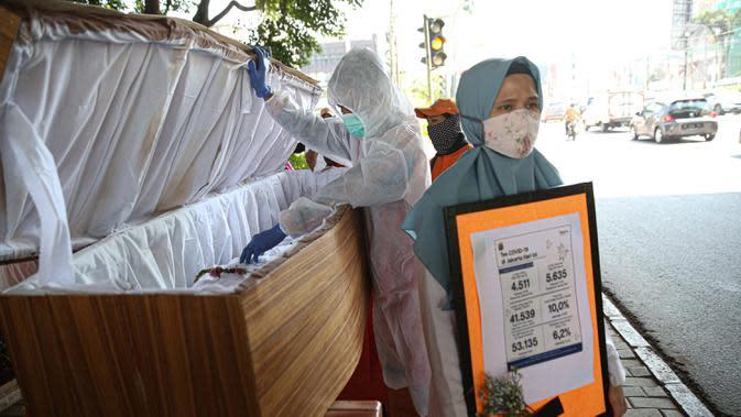 Petugas dari Kecamatan Cilandak membawa peti mati di kawasan fatmawati, Jakarta, Rabu (26/8/2020). Kegiatan tersebut untuk mesosialisasikan bahaya COVID-19 yang dapat menyebabkan kematian. (Liputan6.com/Faizal Fanani)