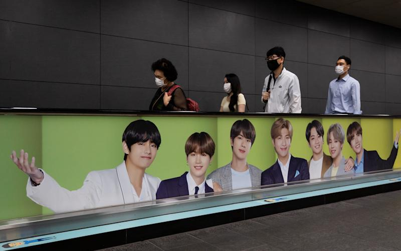 Commuters ride on a travelator featuring an advertisement for K-pop boy band BTS at a subway station in Seoul - Bloomberg