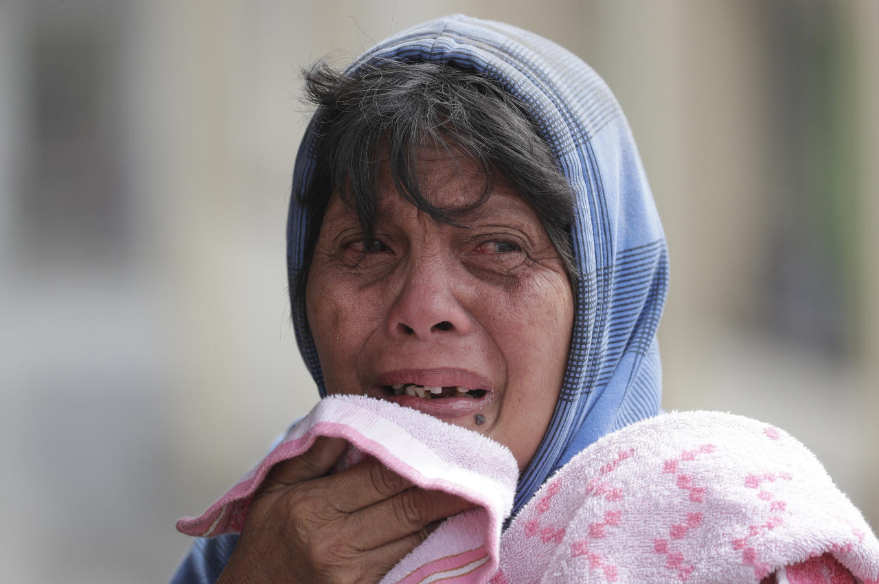 Erman Batan breaks in tears over her missing husband Roberto, who she has not seen since they evacuated their homes near the Taal volcano in Tagaytay, Cavite province, southern Philippines on Monday, Jan. 13, 2020. (AP Photo/Aaron Favila)
