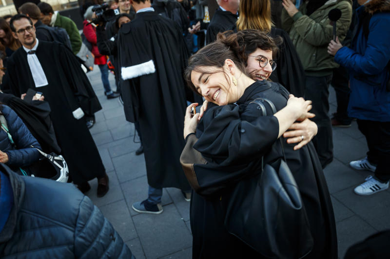 Lawyers Laila Batou, foreground hugs Marie-Pomme Moinat as they celebrate the non-guilty verdict of the trial of 12 pro-climate activists of the LAC collective (Lausanne Action Climat), in front of the tribunal of Renens, in Switzerland, Monday, Jan. 13, 2020.  A Swiss court on Monday threw out a case against a dozen climate activists who were on trial for storming a Credit Suisse office in Lausanne, Switzerland, and playing tennis inside — part of a protest against the bank's investments in fossil fuels that has ensnared its brand ambassador Roger Federer. (Valentin Flauraud/Keystone via AP)