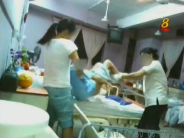 Two staff are seen carrying the old woman and throwing her onto her bed. (YouTube)