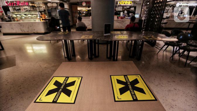 Tanda pembatas jaga jarak di meja area makan di Senayan City, Jakarta, Selasa (9/6/2020). Senayan City siap menyambut pengunjung kembali pada 15 Juni 2020 dengan menerapkan protokol pencegahan COVID-19 seperti pengecekan suhu tubuh hingga sensor tanpa sentuh untuk lift. (Liputan6.com/Johan Tallo)