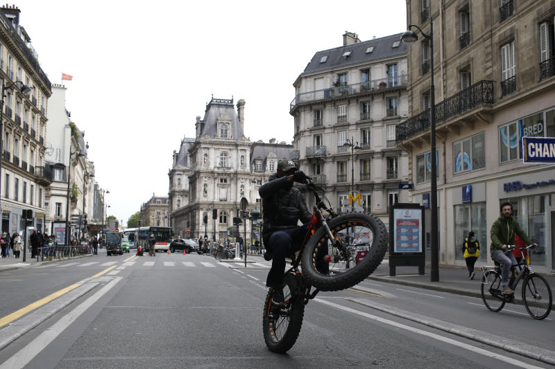 A boys performs a wheeling with his bicycle in empty street Monday, May 11, 2020 in Paris. The French began leaving their homes and apartments Monday for the first time in two months without permission slips as the country began cautiously lifting its virus lockdown. (AP Photo/Rafael Yaghobzadeh)
