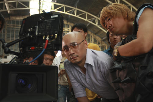 """In this publicity image released by Pegasus Motion Pictures, """"Lost in Thailand"""" director, writer and star Xu Zheng, center, checks a monitor with his co-star Wang Baoqiang, right. The director of China's biggest box-office hit, says """"Lost in Thailand"""" succeeded by showing a rarely seen subject: modern Chinese life. The historical epic, fantasy, action and thriller genres have long filled China's domestic movie screens. But """"Lost in Thailand"""" was a low-budget and light-hearted road-trip tale about an ambitious executive who goes to Thailand to get his boss's approval for a business deal. Along the way he's pursued by a rival co-worker and encounters a wacky tourist who helps him rethink his priorities. (AP Photo/Pegasus Motion Pictures)"""
