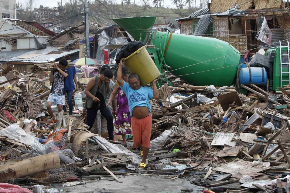 Residents walk past devastated houses after super typhoon Haiyan hit Tacloban