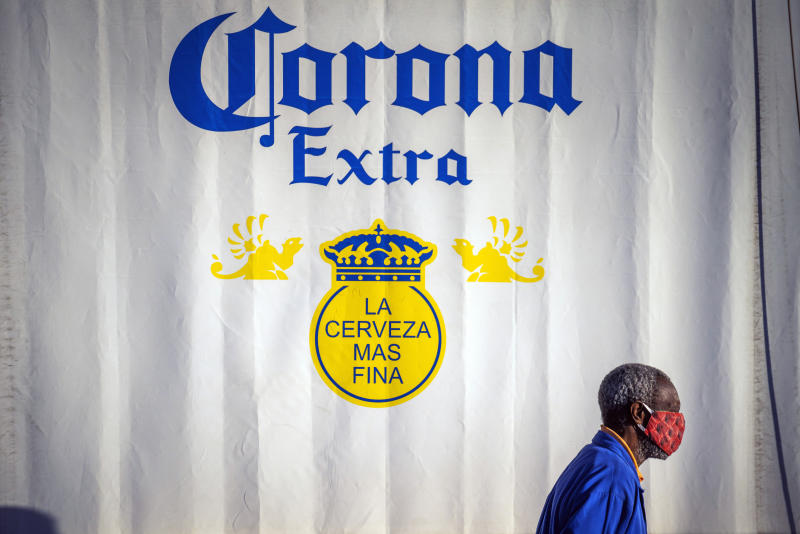 FILE - In this May 18, 2020, file photo, a resident of the township of Soweto outside Johannesburg, South Africa, walks in front of a closed bar advertising Corona beer. A bootlegging culture has sprung up across South Africa in response to the government's nearly 8-week-old ban on the sale of cigarettes and alcohol. The restrictions are part of its lockdown to combat the spread of the coronavirus. (AP Photo/Jerome Delay, File)
