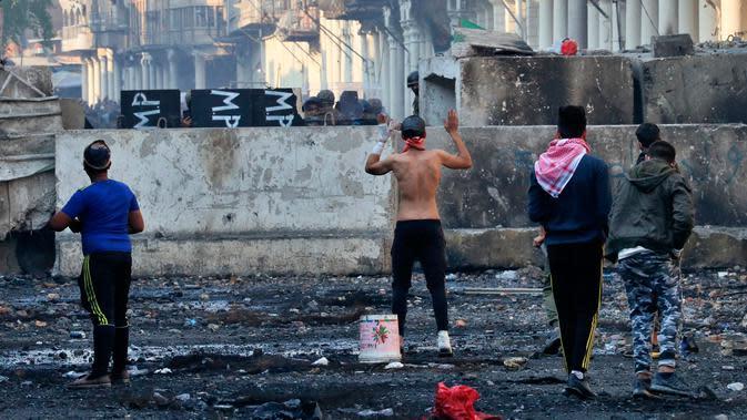 Polisi antihuru-hara meminta para pengunjuk rasa mundur saat bentrokan di Rasheed Street, Baghdad, Irak, Kamis (28/11/2019). Sebanyak 27 demonstran antipemerintah tewas ditembak mati oleh pasukan keamanan Irak dalam sehari. (AP Photo/Khalid Mohammed)