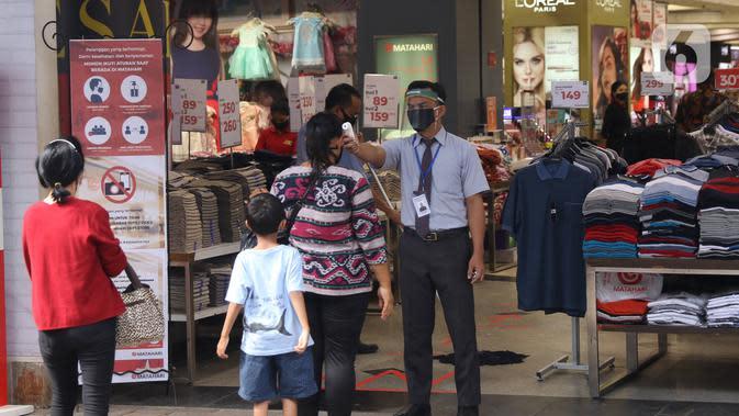 Petugas mengukur suhu pengunjung sebelum memasuki salah satu pertokoan di Pasar Baru, Jakarta Pusat, Selasa (9/6/2020). Pusat perbelanjaan tersebut kembali dibuka, meski masih dalam masa Pembatasan Sosial Berskala Besar (PSBB) transisi. (Liputan6.com/Angga Yuniar)