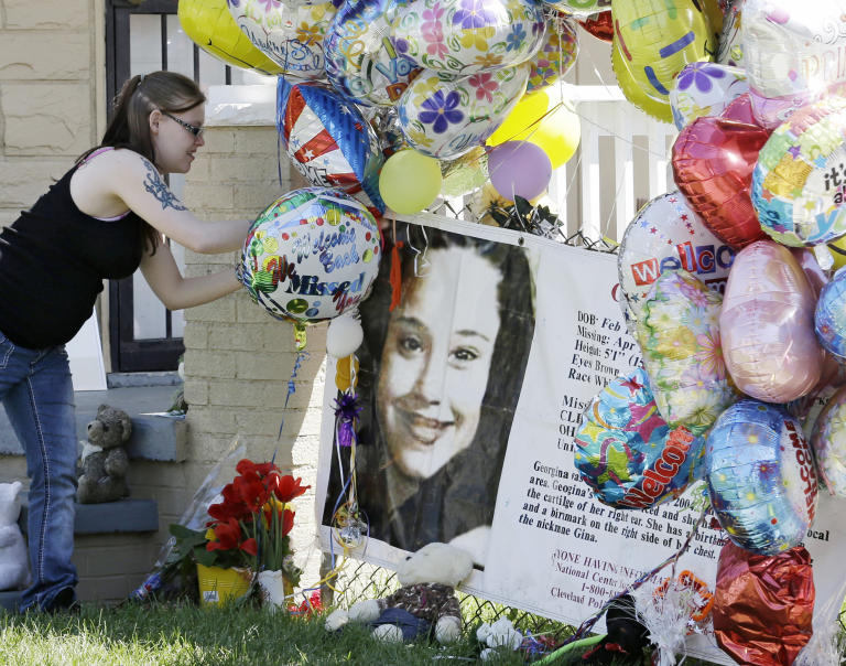 A girl adds a balloon outside the home of Gina DeJesus Thursday, May 9, 2013, in Cleveland. Ariel Castro, the man accused of raping and kidnapping DeJesus and 2 other women, who were missing for about a decade before being found alive at his home, was ordered held Thursday on $8 million bail. (AP Photo/Tony Dejak)