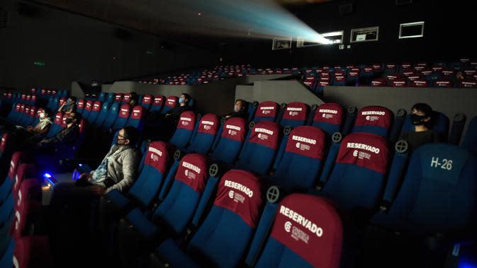 Orang-orang yang memakai masker menonton film di bioskop Cineteca Nacional saat pelonggaran pembatasan di Mexico City, Rabu (12/8/2020). Setelah ditutup hampir lima bulan akibat Corona, bioskop di ibu kota Meksiko dibuka kembali dengan kapasitas 30 persen. (ALFREDO ESTRELLA/AFP)