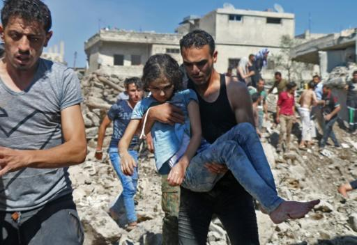 A man carries a child rescued after earlier Syrian regime and Russian air strikes in the rebel-held town of Nawa on June 26, 2018