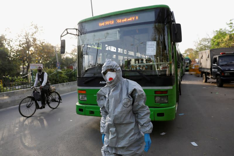 A driver wearing a protective suit walks in front of a bus carrying suspected carriers of coronavirus disease to a quarantine facility, amid concerns about the spread of coronavirus disease (COVID-19), in Nizamuddin area of New Delhi