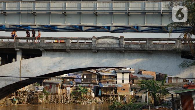 Anak-anak bermain di jembatan Sungai Ciliwung, Jakarta, Senin (5/10/2020). Pemprov DKI mencatat kenaikan angka kemiskinan Jakarta sebesar 1,11 persen menjadi 4,53 persen pada bulan September 2020 karena terdampak pandemi COVID-19. (Liputan6.com/Immanuel Antonius)