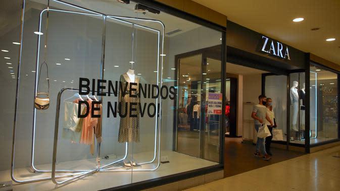 Sepasang suami istri keluar dari toko pakaian di Abasto Shopping Mall di Buenos Aires, Argentina, Rabu (14/10/2020). Setelah tujuh bulan ditutup, pusat perbelanjaan Buenos Aires dibuka kembali saat lonjakan kasus COVID-19 terjadi di pedalaman negara itu. (AP Photo/Victor R. Caivano)