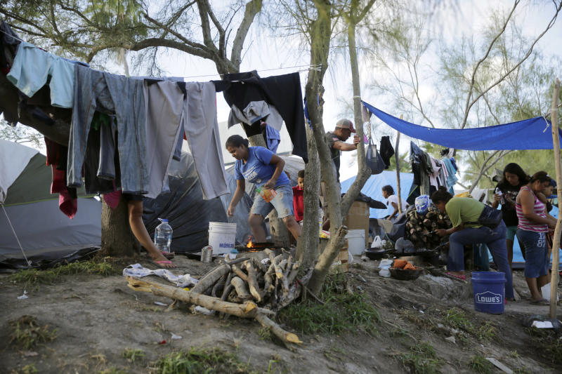 In this Tuesday, Nov. 5, 2019, photo, migrants live in a refugee camp in Matamoros, Mexico. One by one, asylum-seekers from El Salvador and Honduras who are waiting in Mexico for court hearings in the United States appeared before an immigration judge to explain why, after months of effort, they couldn't find an attorney.  (AP Photo/Eric Gay, File)