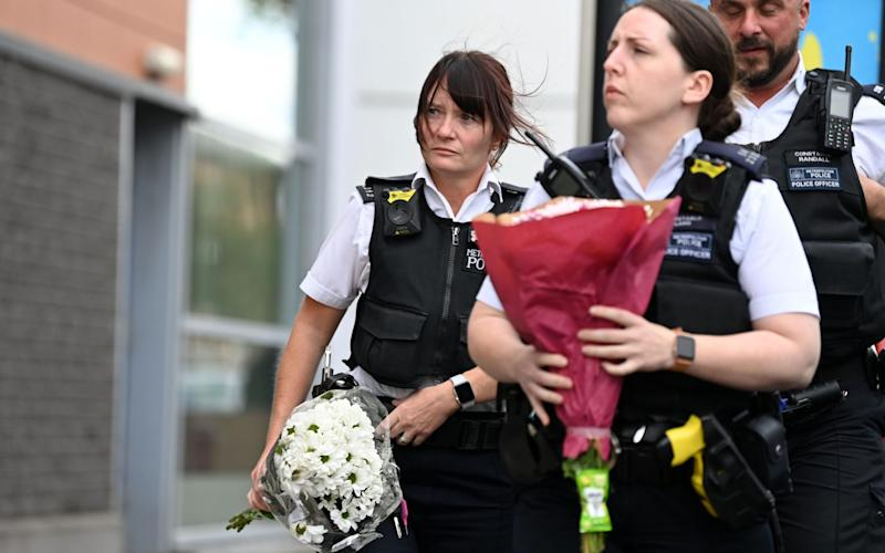 Police officers bring floral tributes to the Croydon Custody Centre in south London  - DANIEL LEAL-OLIVAS/AFP via Getty Images