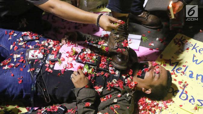 Wartawan melakukan aksi teatrikal tolak kekerasan jurnalis di depan Istana Merdeka, Jakarta, Kamis (26/9/2019). Mereka mengecam kekerasan terhadap jurnalis oleh kepolisian saat peliputan unjuk rasa di Gedung DPR. (Liputan6.com/Angga Yuniar)