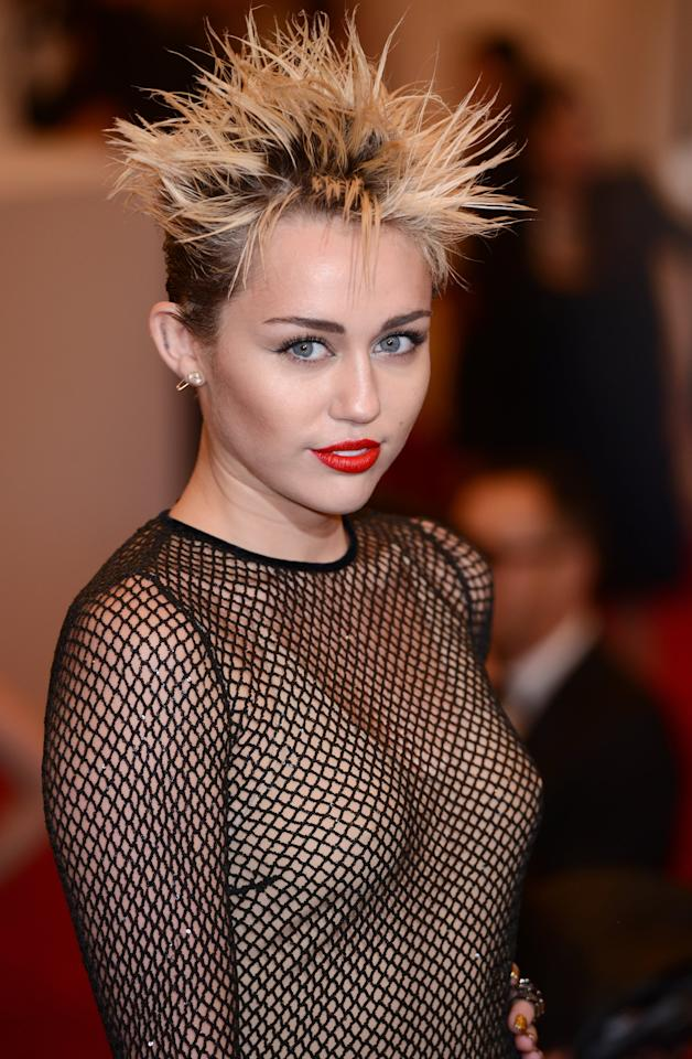 """<p><a class=""""sugar-inline-link ga-track"""" title=""""Latest photos and news for Miley Cyrus"""" href=""""https://www.popsugar.com/Miley-Cyrus"""" target=""""_blank"""" data-ga-category=""""Related"""" data-ga-label=""""https://www.popsugar.com/Miley-Cyrus"""" data-ga-action=""""&lt;-related-&gt; Links"""">Miley Cyrus</a>'s interpretation of 2013's theme - """"Punk: Chaos to Couture"""" - was spot on with her spiked-up hair and bold red lip.</p>"""