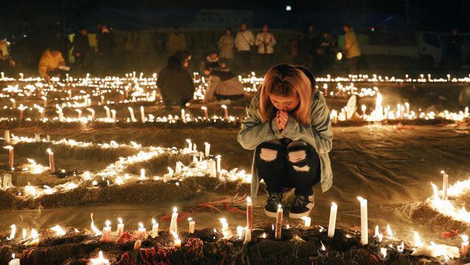 Seorang wanita berdoa di sebuah taman selama memperingati 25 tahun gempa Hanshin Besar di Itami, dekat Kobe, Jepang bagian barat (17/1/2020). Gempa Bumi besar Hanshin-Awaji adalah gempa Bumi yang terjadi di Jepang pada tanggal 17 Januari 1995 pukul 5:46:42 pagi. (Kyodo News via AP)