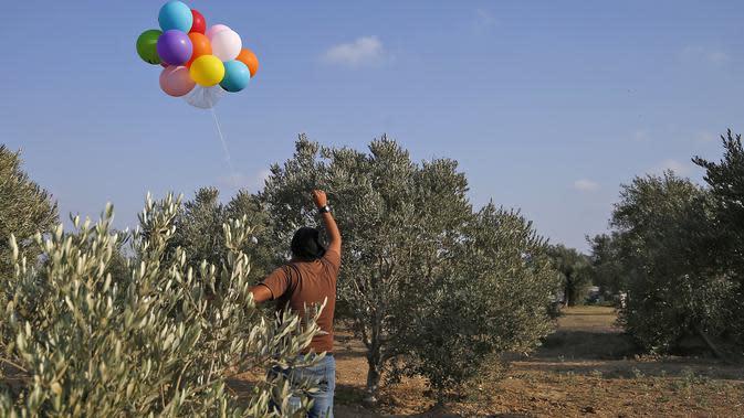 Seorang pria Palestina melepaskan balon dengan alat peledak ke arah Israel di sepanjang perbatasan Israel-Gaza (12/8/2020). Imbas gempuran balon api, Israel melancarkan serangan balasan yang menyasar pertahanan Hamas serta menghentikan pasokan bahan bakar ke Jalur Gaza. (AFP Photo/Mohammed Abed)