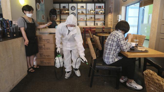 Pekerja mendisinfeksi kafe di Goyang, Korea Selatan, Selasa (25/8/2020). Korea Selatan menutup sekolah dan beralih kembali ke pembelajaran jarak jauh setelah memasuki hari ke-12 peningkatan berturut-turut dalam kasus COVID-19. (AP Photo/Ahn Young-joon)