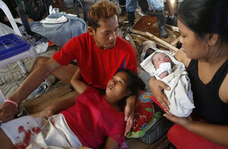 A relative holds newly born baby Beatriz as her mother recuperates at a makeshift birthing clinic in Tacloban city in central Philippines