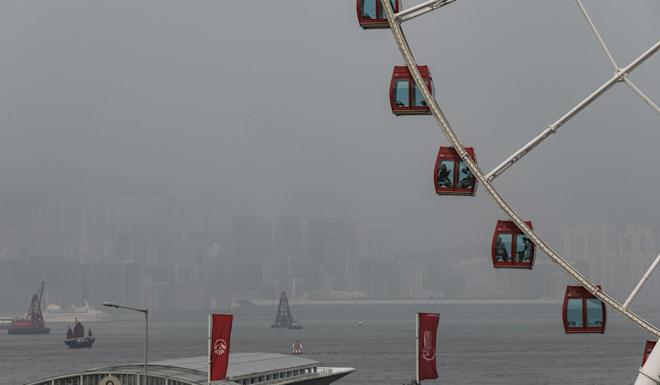 Kowloon is barely visible across Victoria Harbour from the waterfront in Central on a smoggy day in 2019. Photo: Sam Tsang