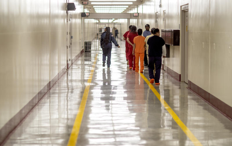 In this Nov. 15, 2019, photo, detainees walk through the halls at the Stewart Detention Center, in Lumpkin, Ga. The rural town is about 140 miles southwest of Atlanta and next to the Georgia-Alabama state line. The town's 1,172 residents are outnumbered by the roughly 1,650 male detainees that U.S. Immigration and Customs Enforcement said were being held in the detention center in late November. (AP Photo/David Goldman)