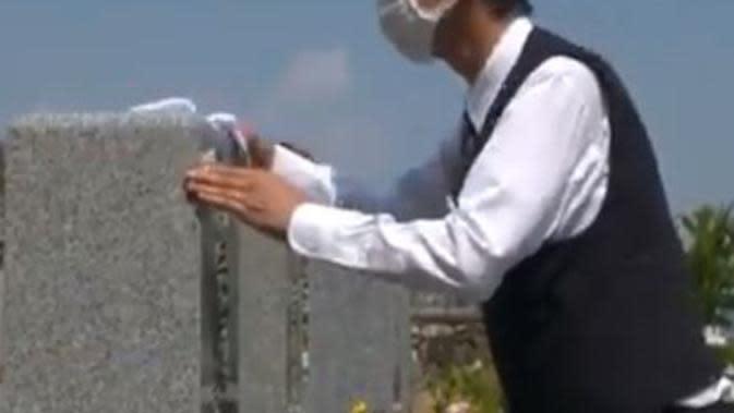 Sopir taksi asal Jepang membersihkan makam klien. (dok. screenshot video Twitter @SCMPNews)