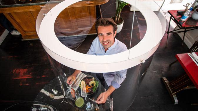 Christophe Gernigon berpose di bawah penemuannya, purwarupa gelembung plexiglass Plex'Eat di restoran H.A.N.D di Paris, pada 27 Mei 2020. Plex'Eat dapat disesuaikan dengan semua jenis tempat usaha dan butik serta tempat-tempat umum untuk melindungi dari pandemi COVID-19. (Xinhua/Aurelien Morissard)
