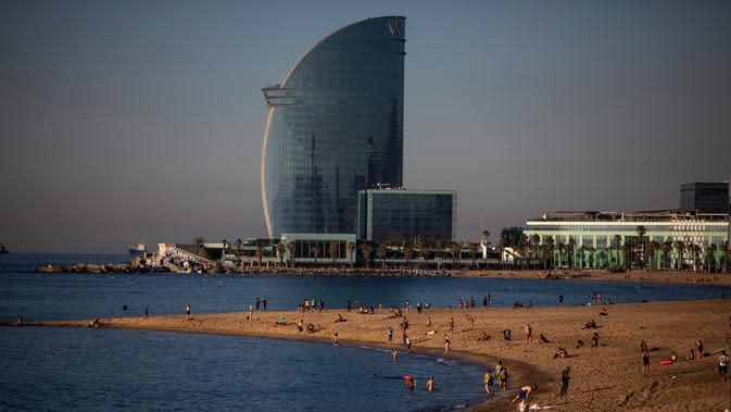 Orang-orang menikmati pantai di Barcelona, Spanyol, Rabu, (20/5/2020). Barcelona mengizinkan orang untuk berjalan di pantai Rabu, untuk pertama kalinya sejak dimulainya penutupan virus lebih dari dua bulan lalu. Berjemur dan berenang rekreasi masih tidak diizinkan. (AP Photo/Emilio Morenatti)