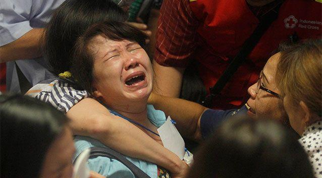 Relatives of passengers of the missing AirAsia flight QZ 8501 react to the news on television about the findings of bodies on the waters near the site where the jetliner disappeared. Photo: AP