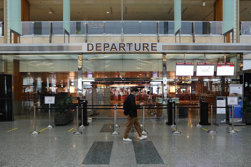 SINGAPORE - APRIL 30: A man wearing a protective mask walks past a closed departure gate at Changi Airport Terminal 2 on April 30, 2020 in Singapore. Changi Airport Terminal 2 will suspend operations from May 1, 2020 for 18 months as the coronavirus (COVID-19) outbreak impacted the global travel and aviation sector. (Photo by Suhaimi Abdullah/Getty Images)