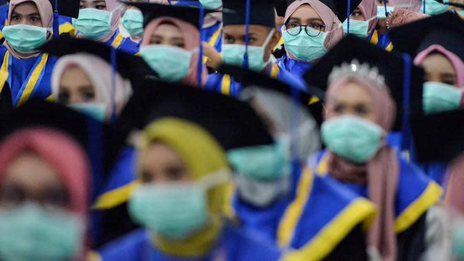 Sejumlah pelajar yang memakai masker sebagai tindakan pencegahan terhadap virus corona COVID-19 mengikuti acara wisuda SMK Farmasi di Banda Aceh (24/9/2020). (AFP/Chaideer Mahyuddin)