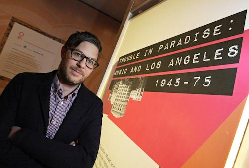 "This March 26, 2012 photo shows Josh Kun, professor of Communications and Journalism at the University of Southern California, posing with the exhibit he curated, ""Trouble In Paradise: Music and Los Angeles, 1945-1975,"" at the Grammy Museum in downtown Los Angeles. The museum website says the exhibit focuses on the ""tensions between alluring myths of Southern California paradise and the realities of social struggle that characterized the years following WWII."" (AP Photo/Reed Saxon)"