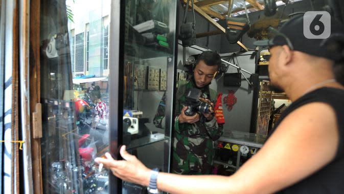 Warga melihat kamera bekas di Kebayoran Vintage, Jakarta, Rabu (30/9/2020). Selama masa pandemi penjualan barang-barang bekas rumah tangga di meningkat hingga 75 % dimana warga menjual barang-barang miliknya untuk mencukupi kebutuhan hidup sehari-hari. (merdeka.com/Arie Basuki)