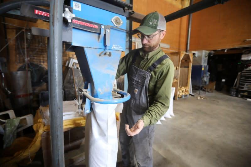 Farm manager fills bags of chicken feed at the Yukon Grain Farm near Whitehorse