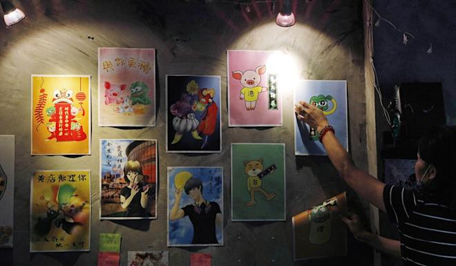 An employee removes stickers and posters with messages in support of the anti-government movement at a restaurant in Hong Kong on July 2, a day after Beijing's sweeping new national security law for Hong Kong went into effect. Photo: AP
