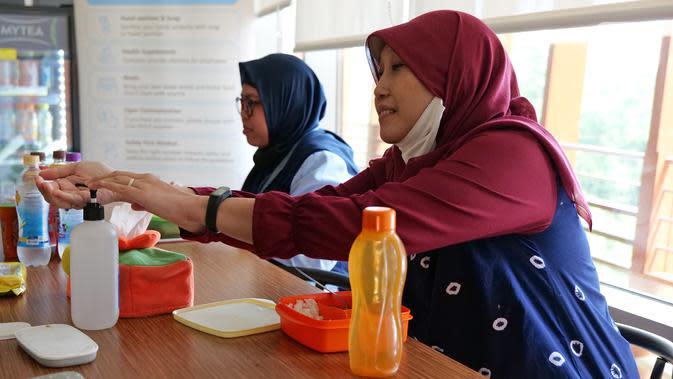 Karyawan menggunakan cairan pembersih tangan sebelum menikmati makan siang di ruang istirahat kantor Suntory Garuda, Jakarta, Senin (8/8/2020). Suntory Garuda menerapkan protokol Kesehatan, salah satunya kapasitas karyawan hanya dibolehkan sebanyak 50 persen. (Liputan6.com/Herman Zakharia)