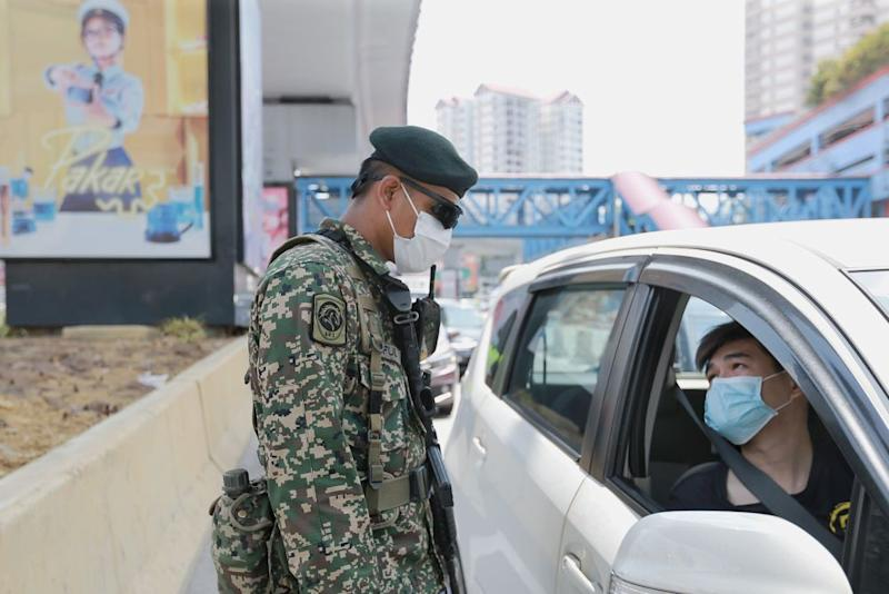 An Armed Forces personnel conducts checks on a vehicle during a roadblock in Petaling Jaya April 1, 2020. — Picture by Ahmad Zamzahuri