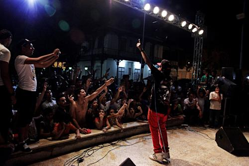 """In this Thursday, June 6, 2013 photo, fans of """"Mahragan"""" music, rabic word for """"festival,"""" singer, Fifty, react to his performance at the International Film Festival in Ismailia, 139 Kilometers (86 miles) from Cairo, Egypt. A new musical sound emerged from the underground in Egypt since the country's 2011 revolution, a rapid-fire electronic beat, mixed with hypnotic rhythms drawn from religious festivals and fired up with auto-tuned vocals. Besides getting club crowds dancing all night long, it has given a rebellious voice to long marginalized youth, telling stories of everyday life in beaten-down neighborhoods of Cairo. (AP Photo/Nariman El-Mofty)"""