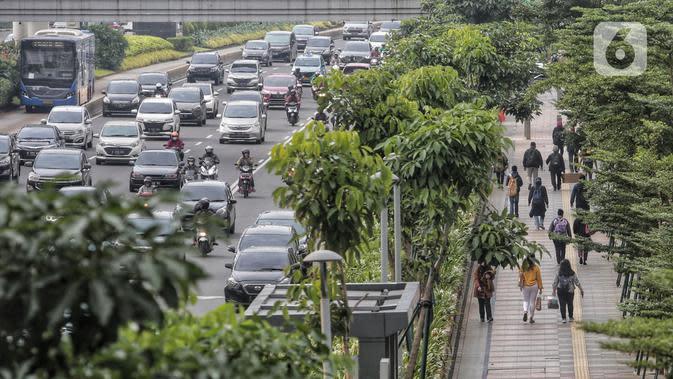 Pegawai pulang kerja berjalan di trotoar Jalan Sudirman, Jakarta, Selasa (12/5/2020). Pemerintah memberi kelonggaran bergerak bagi warga berusia di bawah 45 tahun untuk mengurangi angka pemutusan hubungan kerja (PHK) akibat pandemi virus corona COVID-19. (Liputan6.com/Johan Tallo)
