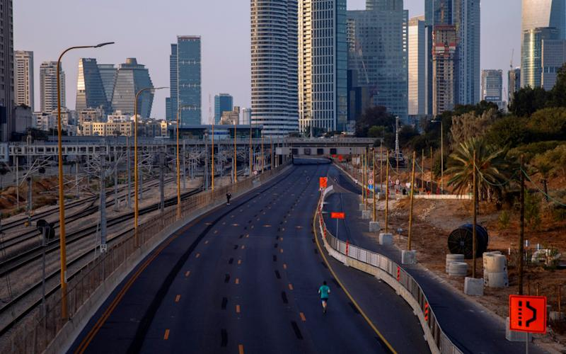 A man runs on a car-free highway, during the Jewish holiday of Yom Kippur, in Tel Aviv - AP