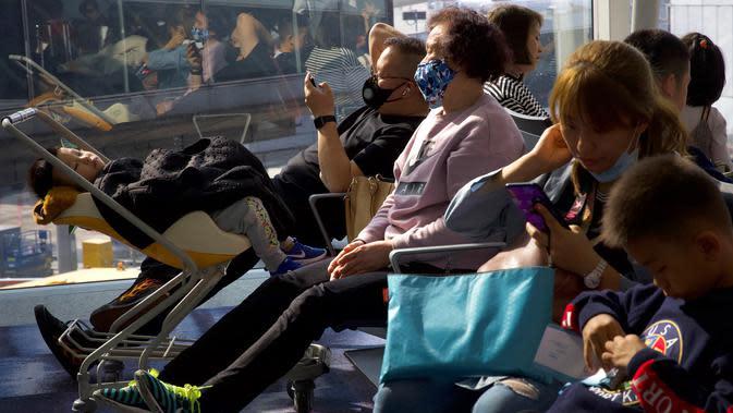 Para pelancong yang mengenakan masker menunggu penerbangan mereka di Bandara Internasional Hong Kong di Hong Kong, Selasa (21/1/2020). Masker terjual habis dan pemeriksaan suhu di bandara dan stasiun kereta api menjadi norma baru di China menyusul merebaknya wabah virus corona. (AP/Ng Han Guan)