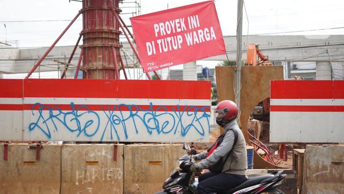 Pengguna jalan melintas di depan poster protes warga terhadap pembangunan flyover di kawasan Tanjung Barat, Jakarta, Rabu (15/7/2020). Dalam poster protes tersebut, warga menuntut agar pembayaran pelunasan pembebasan lahan segera diselesaikan secara serentak. (Liputan6.com/Immanuel Antonius)