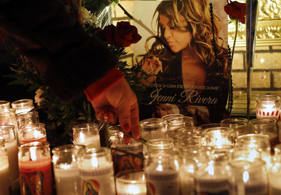 A woman adjusts a flower in front of candles and pictures displayed in tribute to singer Jenni Rivera at the Plaza Mexico shopping center in Lynwood, Calif., early Monday, Dec. 10, 2012. Authorities have not confirmed her death, but Rivera's relatives in the U.S. say they have few doubts that she was on the Learjet 25 that disintegrated on impact Sunday in rugged territory in Nuevo Leon state in northern Mexico. (AP Photo/Patrick T. Fallon)