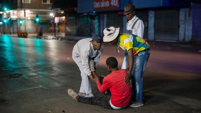 Orang-orang membantu seorang pria yang jatuh setelah dikejar polisi karena melanggar lockdown di pusat kota Johannesburg, Afrika Selatan, Jumat (27/3/2020). (AP Photo/Jerome Delay)