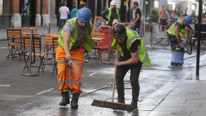 Pekerja membersihkan jalan saat meja dan kursi disiapkan untuk makan di luar ruangan di London setelah Perdana Menteri Inggris Boris Johnson mengumumkan serangkaian pembatasan baru, Kamis (24/9/2020). Aturan pembatasan sosial yang akan beberlangsung selama enam bulan. (AP Photo/Kirsty Wigglesworth)